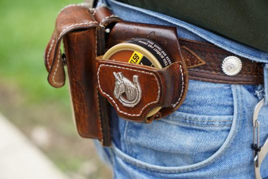 """Smokeless tobacco, """"dip,"""" sits in the side of a holster on Cowboy's belt"""