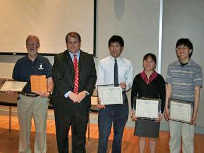 Mark Plummer of Toshiba (second from left), presents first-place plaques to Roger Que, Lisa Zhang, Cory Li (left to right) and their coach, Robert Gotwals, (far left), from the North Carolina School of Math and Science. The team won their age group for the 2008 Toshiba/NSTA ExploraVision Awards Program. (Photo courtesy of www.exploravision.org)