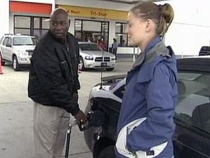 Hoke County Sheriff Hubert Peterkin, left, pumps gasoline for a pedestrian on Friday, Oct. 24, 2008. Peterson paid $4,000 from his re-election campaign to help bring some relief to his citizens, he says.