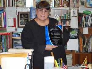 "Gail Legget-Roberson, author of the ""Nature in a Nutshell"" column in The Wake Weekly, received the Dan Wilkinson WRAL Conservation Communication Award. She poses with the award plaque in her office at her Morningstar Nature Refuge in Williamston."