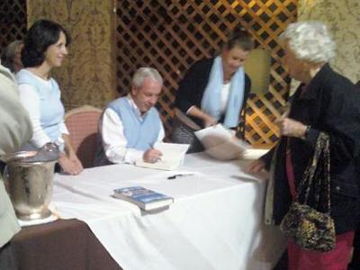 Coach Roy Williams signs copies of his book Tuesday at Fearrington Village in Chapel Hill.