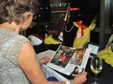 An event-goer at the Caring Community Foundation's Pay-It-Forward gala reads an issue of People magazine, featuring the the charity's founder Jill Wolford and her family. (Photo courtesy of Tim Brown)