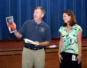 Former NASA astronaut Frank Culbertson presents Stough Elementary Principal Cynthia Keech with photos and patches from his days as an astronaut.
