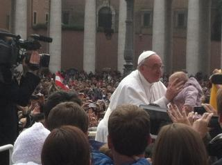 Pope Francis kissing and blessing a baby handed to him by a crowd member as he was driving around following the Mass. (Photo by Michael Shulby)