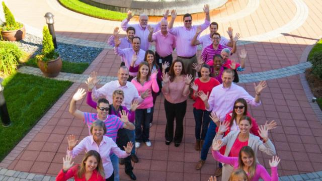 Capitol Broadcasting sales staff  dressed in pink and formed a ribbon to mark Breast Cancer Awareness Month.