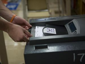 A voter casts his ballot into the machine reader before exiting the Pullen Park polling station in Ralegh.