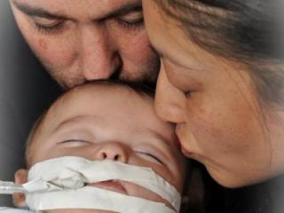Jason and Rachel Degenhard kiss their son, Sonny. (Photo courtesy of the family)