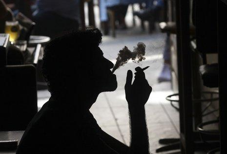 A Turkish man smokes at a bar in Istanbul, Turkey, Monday, May 19, 2008. A law extending a smoking ban in Turkey to most enclosed areas, including taxis, ferries and shopping malls, came into effect Monday in the nicotine-addicted nation. Smoking was already barred on buses and airplanes and in larger offices. A ban on lighting up in bars, restaurants and coffeehouses will be implemented next year. (AP Photo/Serkan Senturk)
