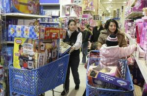 "Maria Eugenia Gomez, left, and Imelda Moreno wheel their carts down the aisle during shopping at the Toys ""R"" Us in North Riverside, Ill., Friday, Nov. 28, 2008. (AP Photo/Charles Rex Arbogast)"