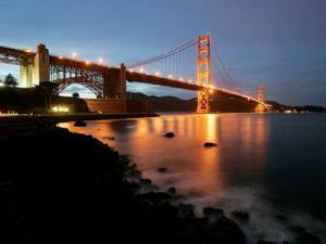 Waves crash on the pier at Fort Point as The Golden Gate Bridge lights up at dusk in San Francisco. (AP Photo/Marcio Jose Sanchez)