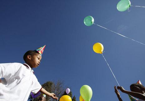 THURSDAY: Children gather to plant a tree in Johannesburg,  in an event organized by the City Parks to celebrate former president Nelson Mandela's birthday. Mandela turns 91 on Saturday. (AP Photo/Denis Farrell)