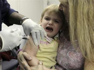 Registered Nurse Constance Joyner gives Anara Lithgow, 2, an H1N1 vaccination as her grandmother Linda McCue holds her at the Wayne County Health Department in Wayne, Mich., Wednesday, Oct. 21, 2009. (AP Photo/Paul Sancya)