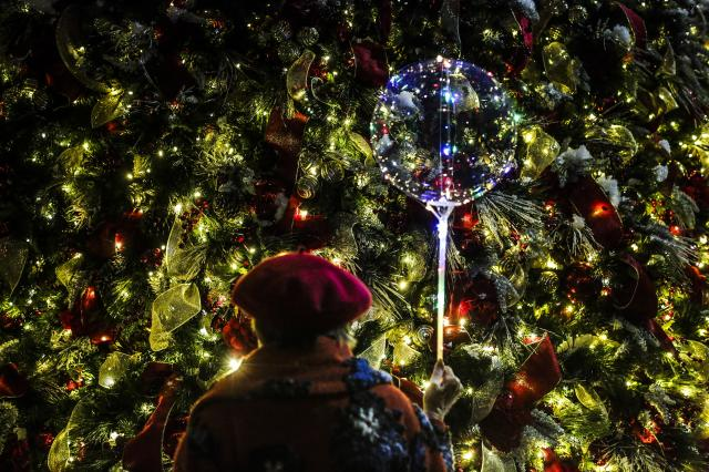 Sibyl McCormac Groff, who leads idiosyncratic Christmas tours in and around Rockefeller Center, holds a balloon and watches a Christmas tree during a tour in New York, Dec. 10, 2017. Groff is a self-directed tour guide of a holiday experience she calls Gothamtide. (Jeenah Moon/The New York Times).
