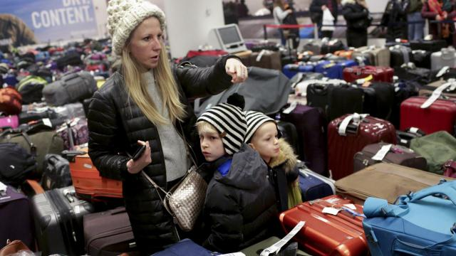 Passengers wade through a large collection of delayed bags at the arrivals hall of Terminal 4 of John F. Kennedy International Airport in New York, Jan. 7, 2018. Delays, cancellations and now flooding has disrupted flights and stranded passengers at the New York airport since Thursday's storm. (Yana Paskova/The New York Times)