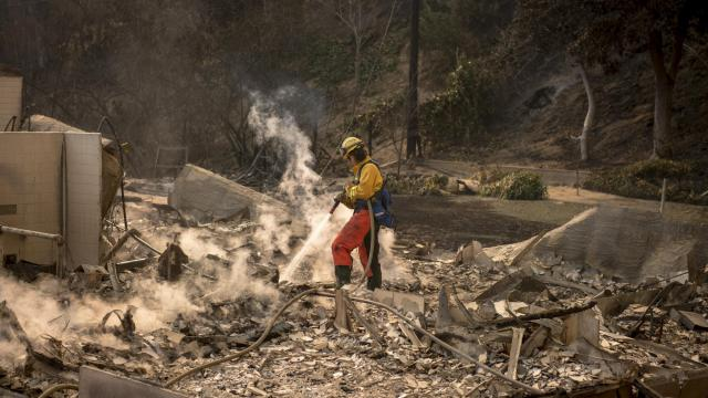 FILE-- A firefighter puts out smoldering fires in a home destroyed by the Thomas Fire, in the foothills of Ventura, Calif., Dec. 6, 2017. Extreme weather events caused a total of $306 billion in damage in the United States last year, making 2017 the most expensive year on record for natural disasters in the country, the National Oceanographic and Atmospheric Administration said Jan. 8, 2018. (Hilary Swift/The New York Times)
