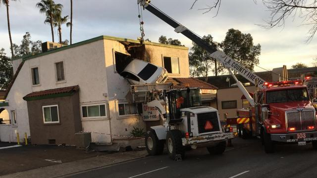 A photo released by the Orange County Fire Authority of workers with heavy equipment removing a Nissan Altima from the second story of a dental office building in Santa Ana, Calif., Jan. 14, 2018. Authorities said the sedan went airborne after clipping a median and that one person was extricated from the car and another was able to exit on his own. (Capt. Stephen Horner/Orange County Fire Authority via The New York Times) -- FOR EDITORIAL USE ONLY.