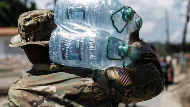 FILE -- Soldiers with the National Guard of Puerto Rico deliver water to residents in Utuado on October 25, 2017. The Federal Emergency Management Agency never intended to end food and water assistance to Puerto Rico on Jan. 31, 2018, a spokesman said, and will continue providing it to Hurricane Maria survivors as needed. (Erika P. Rodriguez/The New York Times)