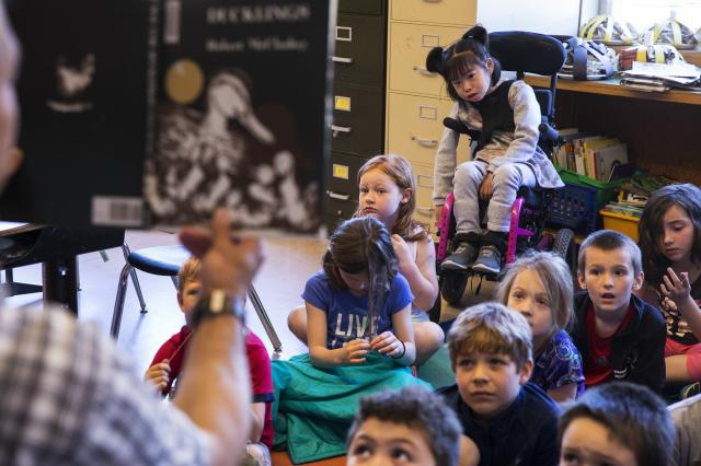 Yuna Lee, who has a rare defect on the FOXG1 gene, listens to a teacher read at Bridlemile Elementary School in Portland, Ore., May 25, 2017. Yuna's mother, Soo-Kyung Lee, who had worked with the FOX family of genes for years, began doing what she was uniquely positioned to do: aiming her research squarely at her daughter's disorder. (Ruth Fremson/The New York Times)