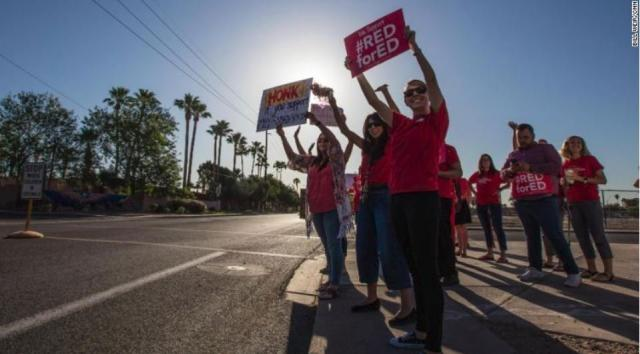 A red sea of Arizona's public school teachers and their supporters marched on the state Capitol in Phoenix Monday, voicing their dissatisfaction over pay and educational funding. The first teacher walkout in the state's history began on Thursday, and Monday night, organizers announced the walkout would enter a fourth day.