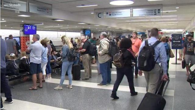 Passengers at the Charlotte airport check their flights after a computer glitch. (Photo: WCNC TV)