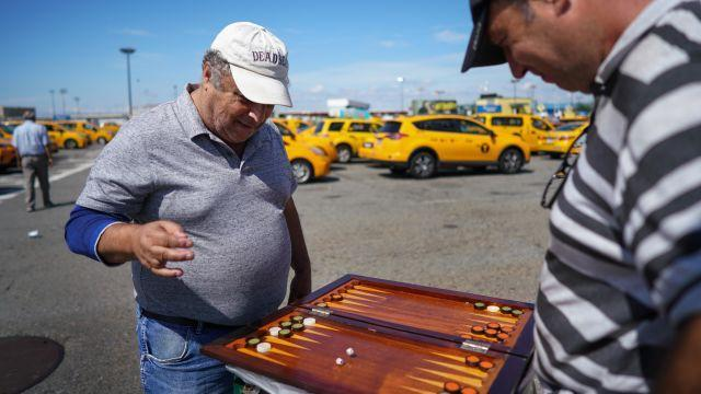 Rabi Musaav, left, and Joseph Kuinov play a game while waiting for their turn at the John F. Kennedy International Airport central taxi hold in New York, July 31, 2018. As New York City moves to limit for-hire vehicles, yellow-cab and Uber drivers are both hopeful that the proposal could ease their financial plight. (Chang W. Lee/The New York Times)