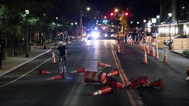 """Protesters threw cones into the road behind them to slow police while marching ahead of the one-year anniversary of the """"Unite the Right"""" rally in Charlottesville, Va., Aug. 11, 2018. A year after the race-fueled violence in Charlottesville, hundreds of demonstrators will gather in a narrow park there on Sunday to denounce racism and hate groups, hours before white nationalists plan to rally in front of the White House. (Erin Schaff/The New York Times)"""