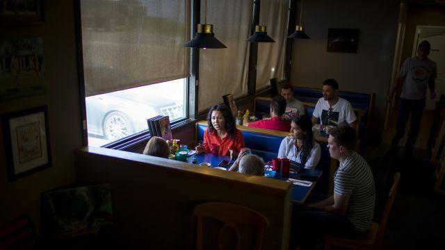 """Xochitl Torres Small, in red, a Democratic House candidate, speaks with voters at a pancake house in Alamogordo, N.M., Aug. 8, 2018. Many Democratic midterm hopefuls are bucking the party's national messaging. Small, a natural resources lawyer, plays into residents' feelings that the needs of the rural Southwest are given short shrift. """"I'm trying to make sure that New Mexico is listened to,"""" she said. (Ivan Pierre Aguirre/The New York Times)"""