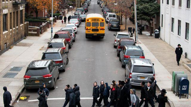 FILE -- A group of school children cross the street in Borough Park in Brooklyn, Nov. 16, 2014. Three years after the city launched an investigation into whether certain ultra-Orthodox Jewish schools were providing an adequate education in secular subjects, it revealed in August 2018 that it had made little progress. (Bryan Thomas/The New York Times)