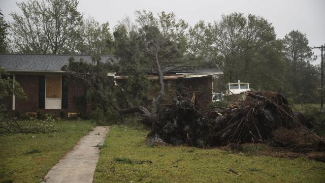 A downed tree on a home as Hurricane Florence swept through the area in Wilmington, N.C., on Sept. 14, 2018. Florence, lashing the North Carolina coast with strong winds and blinding rain, made landfall Friday morning having already driven dangerous storm surges of several feet into beach and river towns. The eye of the storm came ashore at Wrightsville Beach, N.C., just east of Wilmington, with winds of about 90 miles an hour. (Victor J. Blue/The New York Times)