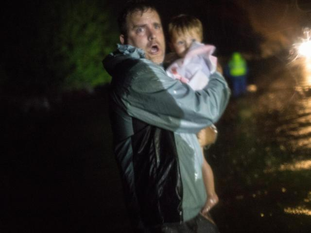 Leonard Harrison carries Dylan Roberts, 2, to safety as he and United Cajun Navy volunteers rescue a family stranded by Hurricane Florence's rising floodwaters in Wilmington, N.C., Sept. 15, 2018. Volunteers took to boats along darkened streets, guiding residents away from waist-high waters brought by the powerful storm. (Tamir Kalifa/The New York Times)