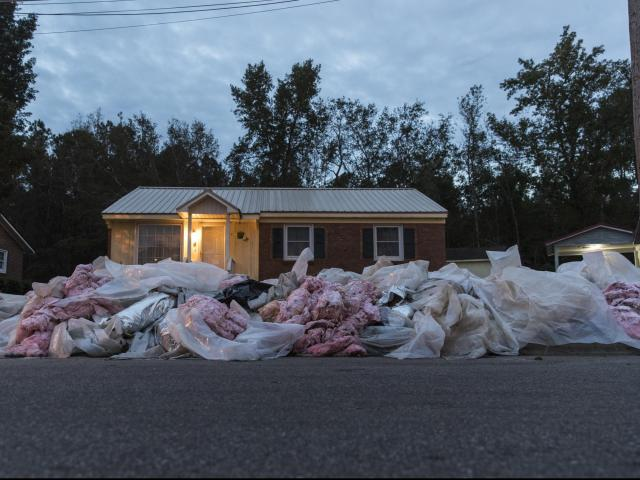 Debris from a gutted house sits on a curb in Lumberton. Residents and towns are struggling to rebuild after Hurricane Florence. (Victor J. Blue/The New York Times)
