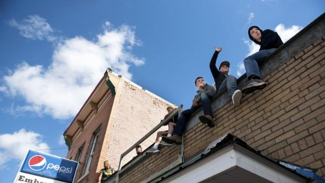 Parade-goers find places on a roof for a homecoming parade in Blanchardville, Wis., Sept. 22, 2018. As Scott Walker, the Republican governor, seeks a third term, Democrats look for a way to successfully make an economic argument in a state where the indicators are strong. (Lauren Justice/The New York Times)