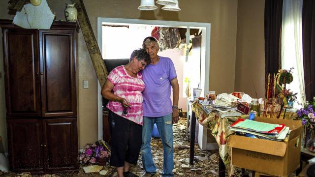 Don and Cherry Holm inside their home, which was damaged by Hurricane Michael, in Marianna, Fla., Oct. 20, 2018. The feeling of being hurried and eventually left behind — the normalizing of catastrophe — is an increasing worry for people caught between a short-attention-span country that lately has seen one disaster after another and the long-term effort to rebuild battered lives. (Saul Martinez/The New York Times)