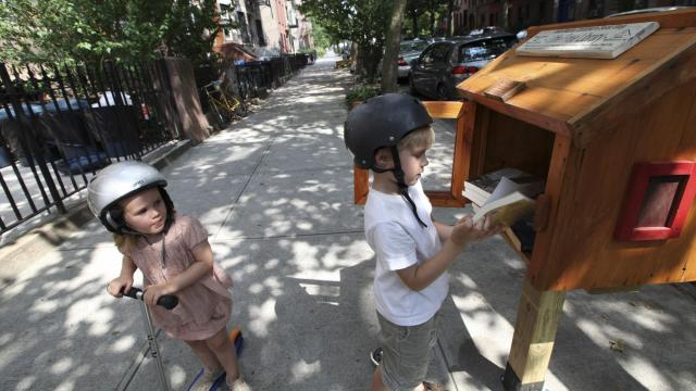 FILE -- Children browse books in a Little Free Library in the Prospect Heights neighborhood of Brooklyn, July 16, 2012. Todd Bol, who filled a handcrafted box in his front yard with books and created the Little Free Library movement that now includes more than 75,000 like it in 88 countries, died on Oct. 18, 2018, in Oakdale, Minn. He was 62. (Marilynn K. Yee/The New York Times)