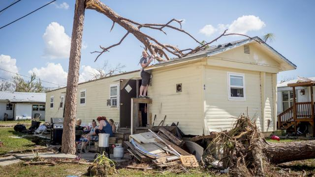 FILE -- Eric Sherred helps a family in a trailer tarp the hole in their roof after Hurricane Michael in Panama City, Fla., Oct. 16, 2018. Residents and officials from Panama City are urging the Federal Emergency Management Agency to speed up its response to a worsening housing crisis that has left thousands homeless or living in buildings damaged when Hurricane Michael tore through the Panhandle nearly three weeks ago. (Emily Kask/The New York Times)