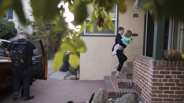 Elizabeth Yura carries her daughter, Charlotte, 2, to inside her home in Alameda, Calif., Oct. 23, 2018. Yura spent hours commuting to Sacramento while pregnant with her daughter. She has changed jobs, but commuting still takes time away from family time. (Brian L. Frank/The New York Times)