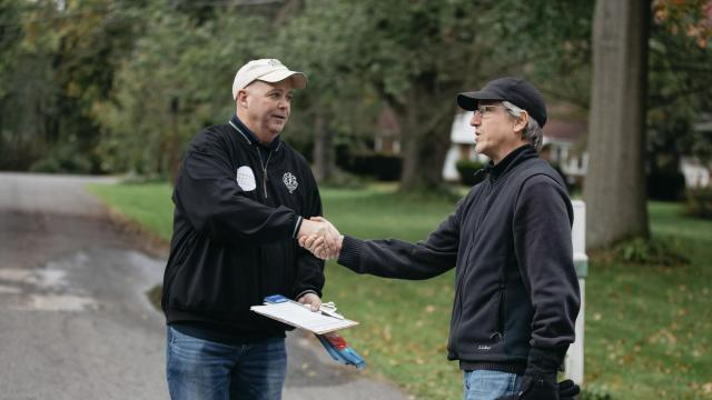 Russ Brode, left, the president of the Tri-County Regional Labor Council, speaks with a voter while canvassing for Richard Cordray, the Democratic candidate for Ohio governor, in Akron, Ohio, Oct. 13, 2018. Few statewide results alarmed Democrats in 2016 more than Ohio. Now they are honing what they hope is a winning economic message focused on workers. (Allison Farrand/The New York Times)