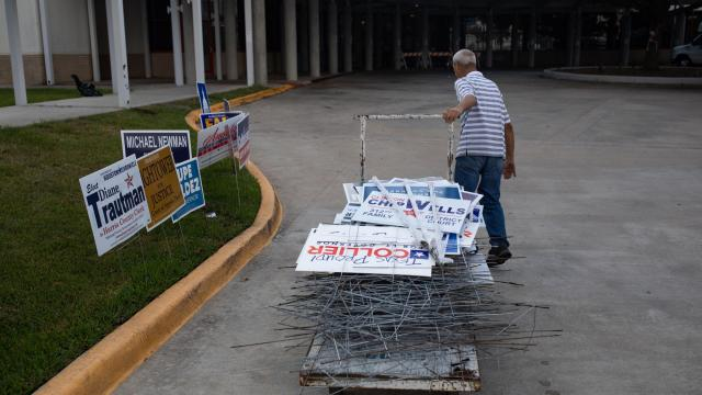Albert Remy removes political campaign signs from the area outside of a polling place the morning after Election Day in Houston, Nov. 7, 2018. (Tamir Kalifa/The New York Times)