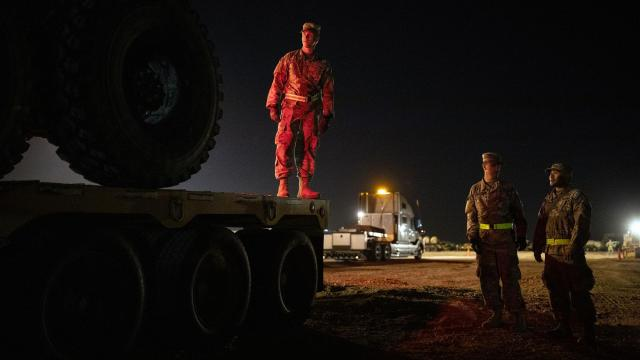 U.S. Army soldiers guide a military vehicle onto a trailer at Base Camp Donna, one of multiple military bases being set up along the U.S.-Mexico border, in Donna, Texas, on Nov. 8, 2018. With little electricity, no combat pay and holidays away from home, the 5,600 American troops on the southwest border are on a mission ordered by a politically determined commander in chief and a Pentagon unable to convince him of its perils. (Tamir Kalifa/The New York Times)