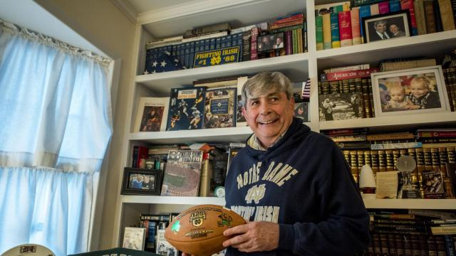 "Joseph Delaney, a Notre Dame football superfan, holds a football from one of the university's undefeated seasons in his basement, which has a shrine to the Fighting Irish, in New York, Nov. 5, 2018. Notre Dame has a legion of devoted football fans who root for the school even though they did not attend it. They are known as ""subway alums."" (Johnny Milano/The New York Times)"