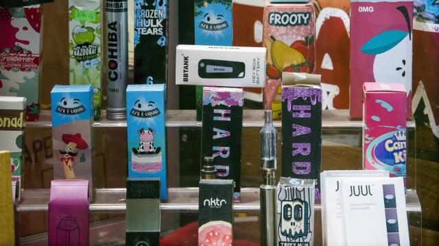Flavored e-cigarette and vape products on display for sale at a store in New York, Nov. 14, 2018. Stopping short of its threatened ban on flavored e-cigarettes, the Food and Drug Administration said on Nov. 15 that it would allow stores to continue selling the products, but only from closed-off areas that are inaccessible to minors. At the same time, the agency moved to outlaw two traditional tobacco products that disproportionately harm African Americans: menthol cigarettes and flavored cigars. (Joshua Bright/The New York Times)
