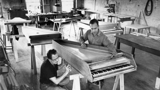 """FILE — Wolfgang Zuckermann, right, with Jules Antonsen, preparing a hand-made harpsichord in New York in September 1958. Zuckermann, a piano technician and self-taught builder whose book """"The Modern Harpsichord"""" helped revive interest in the archaic instrument, died at home in France on Oct. 31, 2018. He was 96. (Neal Boenzi/The New York Times)"""