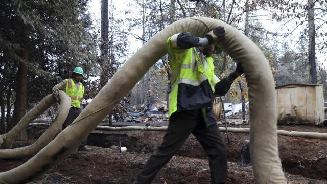 Workers install a waddle along a creek to protect it from toxic runoff after the Camp Fire in Paradise, Calif., Nov. 26, 2018. Heavy metals, chemicals and biological contaminants left behind demand a cleanup of extraordinary scale, before any return to Paradise is safe. (Jim Wilson/The New York Times)