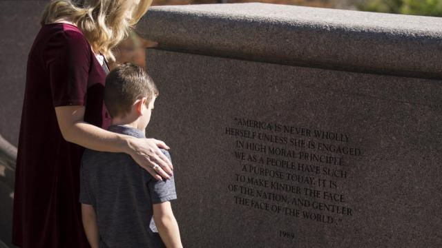 Jackson Connery, 8, and his mother, Leigh Anne Connery, read a quote by former President George H.W. Bush at the George H.W. Bush Monument in Houston, Dec. 1, 2018. The former president was a natural fit with Houston, a city he revered and supported as much as it did him. (Michael Stravato/The New York Times)