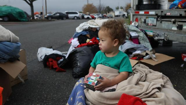 Rebecca Young, 1, sits on a pile of donated clothes in the parking lot outside a Walmart in Chico, Calif., Nov. 28, 2018. Butte County already had 2,000 homeless people and a crisis on its hands before the Camp Fire's devastation added tens of thousands more to their ranks. (Jim Wilson/The New York Times)