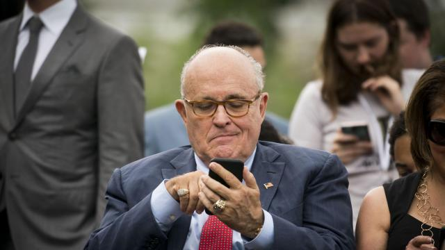 """FILE — Rudy Giuliani, President Donald Trump's attorney, uses a smartphone during an event outside the White House in Washington, May 30, 2018. After Giuliani accidentally tweeted a hyperlink — and a prankster took advantage of it — the president's lawyer baselessly accused Twitter of letting someone """"invade my text."""" (Doug Mills/The New York Times)"""
