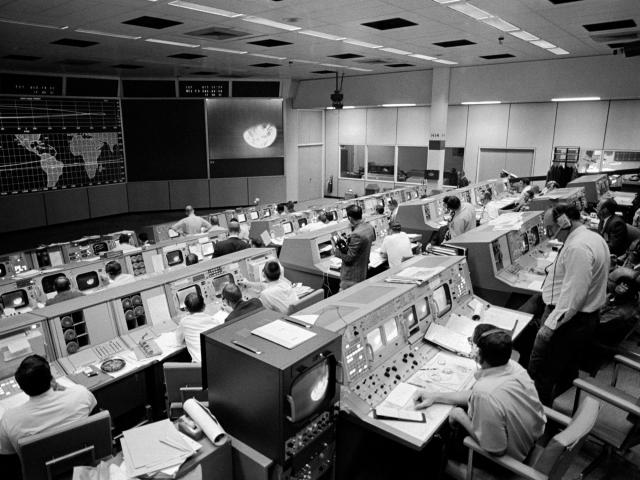 In a handout image from NASA and the Johnson Space Center, an overall view of the Mission Operations Control Room on the third day of the Apollo 8 mission, Dec. 23, 1968. Seen on the television monitor is a picture of Earth which was telecast from the Apollo 8 spacecraft 176,000 miles away. (NASA/Johnson Space Center via The New York Times) -- FOR EDITORIAL USE ONLY. --