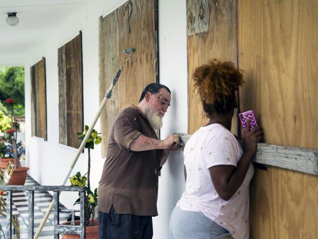 Prudencio Ortiz Aguayo and his daughter Laiza Ortiz board up his home in Maunabo, Puerto Rico, on Wednesday, Aug. 28, 2019, in preparation for the arrival of Tropical Storm Dorian. The storm is expected to slam into the Virgin Islands and northeastern Puerto Rico on Wednesday. (Erika P. Rodriguez/The New York Times)