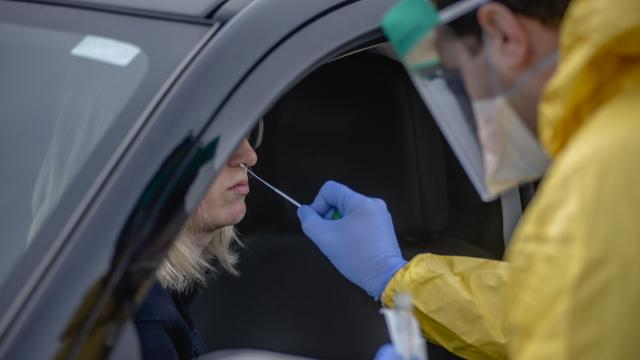 A healthcare worker administers a nasal swab test a drive-thru COVID-19 testing site at ProHEALTH Urgent Care of Jericho, New York, March 18, 2020. Americans must be persuaded to stay home, leading epidemic experts said, and a system put in place to isolate the infected and care for them outside the home; tavel restrictions should be extended; productions of masks and ventilators must be accelerated, and testing problems must be resolved. (Johnny Milano/The New York Times)