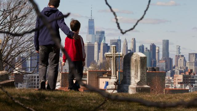Duc Nguyen and his son Otto Nguyen walk through Green-Wood Cemetery in Brooklyn, March 24, 2020. Alarmed by the scale of the coronavirus epidemic in New York City, White House officials advised people who have passed through or left the area to quarantine themselves for 14 days. (Andrew White/The New York Times).